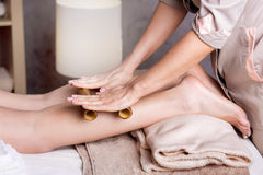 Spa foot massage with bamboo sticks. Woman getting feet massage female therapist with bamboo sticks stock image