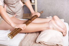 Spa foot massage with bamboo sticks. Woman getting feet massage female therapist  with bamboo sticks Stock Photos