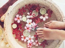 Spa foot treatment. Foot bath in bowl with lime and tropical flowers, spa pedicure treatment, top view stock photography