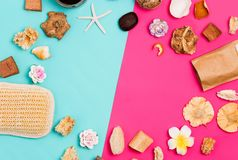 Spa frame made of cosmetic products, washcloths, flowers, seashells, scrub on colorful pink and blue background with copy space fo royalty free stock photo