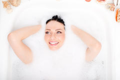 Spa fun: beautiful blue eyes brunette girl attractive young woman relaxing plunged into the foam and happy smiling portrait Stock Photos