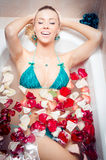 Spa fun: woman in bath with rose petals Stock Photography