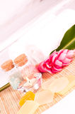 Spa getaway with pink ginger flower and soaps. Spa getaway with pink ginger flower, soaps and bath salts on a hotel bed Stock Image