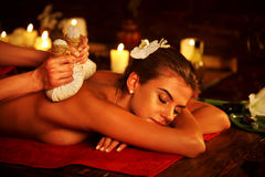 Spa gifts of woman massage in spa salon. Female have herbs hot ball therapy. Stock Photos