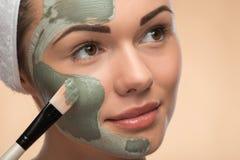 Spa girl with a  towel on her head applying facial Stock Photos