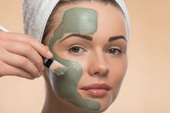 Spa girl with a  towel on her head applying facial Stock Photography
