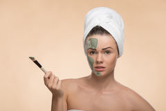 Spa girl with a  towel on her head applying facial Stock Photos