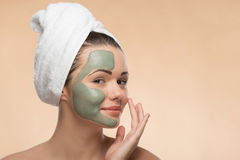 Spa girl with a  towel on her head applying facial Royalty Free Stock Image