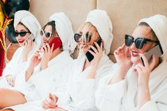 Spa girls smartphone urban leisure lifestyle. Cheerful spa girls talking on smartphones. Urban females leisure lifestyle. Sunglasses, bathrobes and towel turbans royalty free stock photography