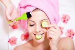 Spa gyckel: closeupbilden av den härliga blonda unga kvinnan för den roliga flickan som har lyckliga le ögon för mång- behandling Royaltyfri Fotografi