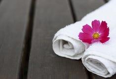 Spa handdukar och blommor på träbakgrund, kopieringsutrymme arkivbild