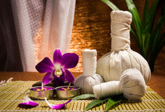 Spa herbal compressing ball with candles and orchid Royalty Free Stock Photo