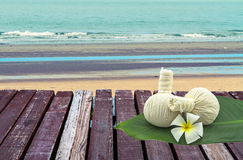 Spa herbal compressing ball and white frangipani flower Apocynaceae,Pagoda tree,Temple treein green leaf on wooden platform Stock Image