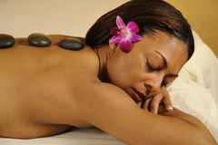 Spa Hot Mineral Stone Massage with Flower in Hair. Woman relaxing at day spa salon during a hot mineral stone massage treatment Royalty Free Stock Photos