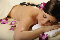 Spa Hot Mineral Stone Massage and Flowers Royalty Free Stock Images