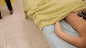Spa Hot Stone Massage. Beautiful girl. Spa Hot Stone Massage. Girl do massage with basalt stones stock video