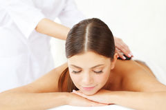 Spa hot stone massage. Young beautiful woman in spa getting hot stone massage Stock Photos