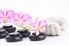 Spa with hot stones, candle and orchids. Hot stones, tea light and orchids close up stock photo