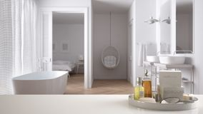 Spa, hotel bathroom concept. White table top or shelf with bathing accessories, toiletries, over blurred classic bathroom, modern. Architecture interior design royalty free stock photo