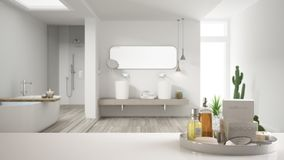 Spa, hotel bathroom concept. White table top or shelf with bathing accessories, toiletries, over blurred minimalist bathroom, mode. Rn architecture interior royalty free stock image