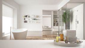 Spa, hotel bathroom concept. White table top or shelf with bathing accessories, toiletries, over blurred minimalist bathroom, mode. Rn architecture interior royalty free stock images