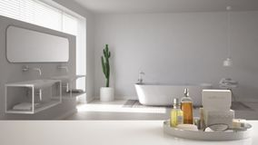 Spa, hotel bathroom concept. White table top or shelf with bathing accessories, toiletries, over blurred minimalist bathroom, mode. Rn architecture interior stock photos