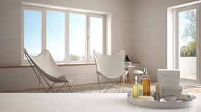 Spa, hotel concept. White table top or shelf with bathing accessories, toiletries, over blurred minimalist rest room. With armchair, modern architecture stock photos