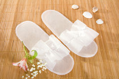 Spa or hotel single use slippers. On a bamboo mat Royalty Free Stock Photography