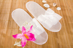 Spa or hotel single use slippers. On a bamboo mat Stock Photography
