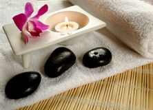 Spa Icons. Aromatic candle, stones, orchid and a white towel Royalty Free Stock Photography