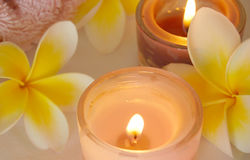 Spa image. Frangipani flowers and lit candles royalty free stock images