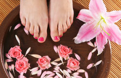 Spa image of female feet and flowers. Spa background with a beautiful legs, flowers, petals and ceramic bowl Stock Images