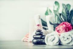 Spa inställning med bunten av massagestenar, blommor, handdukar och palmblad, främre sikt, wellnessbegrepp royaltyfri fotografi
