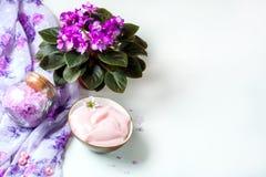 Spa inställning med skönhetsmedelkräm, salt för bad och afrikansk violet i blomkruka på vit trätabellbakgrund Selektivt fokusera Arkivfoto