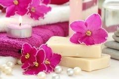 SPA inställning med stearinljus och nya violets Arkivfoton