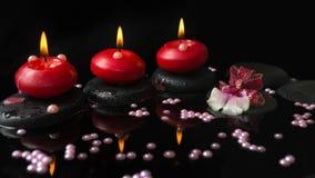 Spa inställning av röda stearinljus, orkidécambriablomma på zenstenar Arkivbild