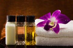 Spa inställning med flaskor och orkidén för handdukarom olje- Arkivfoto