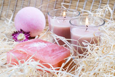 Spa items. On a straw fabric: candles, natural soap, fizzy bath bombs, straw and flower Royalty Free Stock Photo
