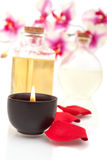 Spa items on white background. Body oils, rose petals and candle on white background Royalty Free Stock Photography
