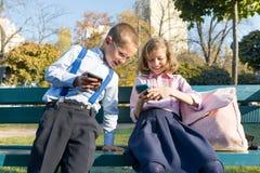 Spa?kinder Junge und M?dchen untersuchen Smartphones Auf einer Bank mit Schulrucksäcken, sonniger Park des Hintergrundherbstes stockfotografie
