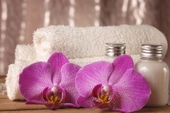 Spa kit with lotions for skin, orchid flowers and white towels.  Stock Photos