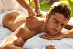 Spa kroppmassage Man som tycker om koppla av tillbaka massage utomhus arkivbild