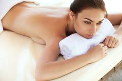 Spa kvinna. Härlig ung kvinna som kopplar av efter massage. Spa sal Arkivbild