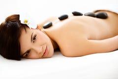 Spa kvinna. Härlig kvinna som får varm stenmassage i Spa Sal Royaltyfri Foto