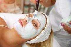 Spa kvinna som applicerar den ansikts- leramaskeringen royaltyfri fotografi