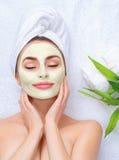 Spa kvinna som applicerar den ansikts- maskeringen arkivfoto