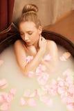 Spa La muchacha toma el baño con la sal del mar y los pétalos color de rosa Imagen de archivo libre de regalías