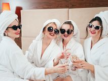 Spa leisure relaxation females bathrobes champagne. Spa leisure time. BFF relaxation. Sunglasses, bathrobes and towel turbans on. Females clinking champagne royalty free stock photo