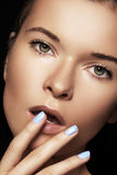 Spa & make-up. Woman face with nails manicure, clean skin Stock Image