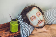 Spa man applying Facial green clay Mask. Beauty Treatments. Fresh green smoothie with banana and spinach with heart of sesame seed Stock Images